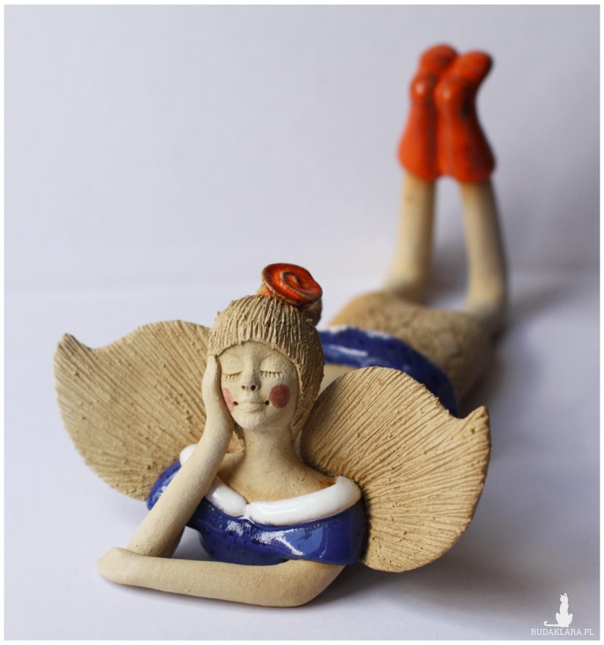 Anioł leżący z różą we włosach