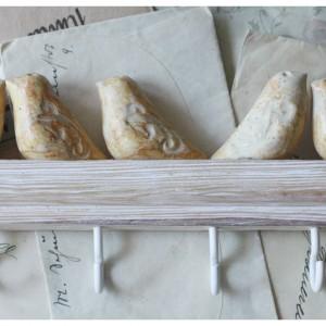 Wieszak z kremowymi ptaszkami na bielonym drewnie