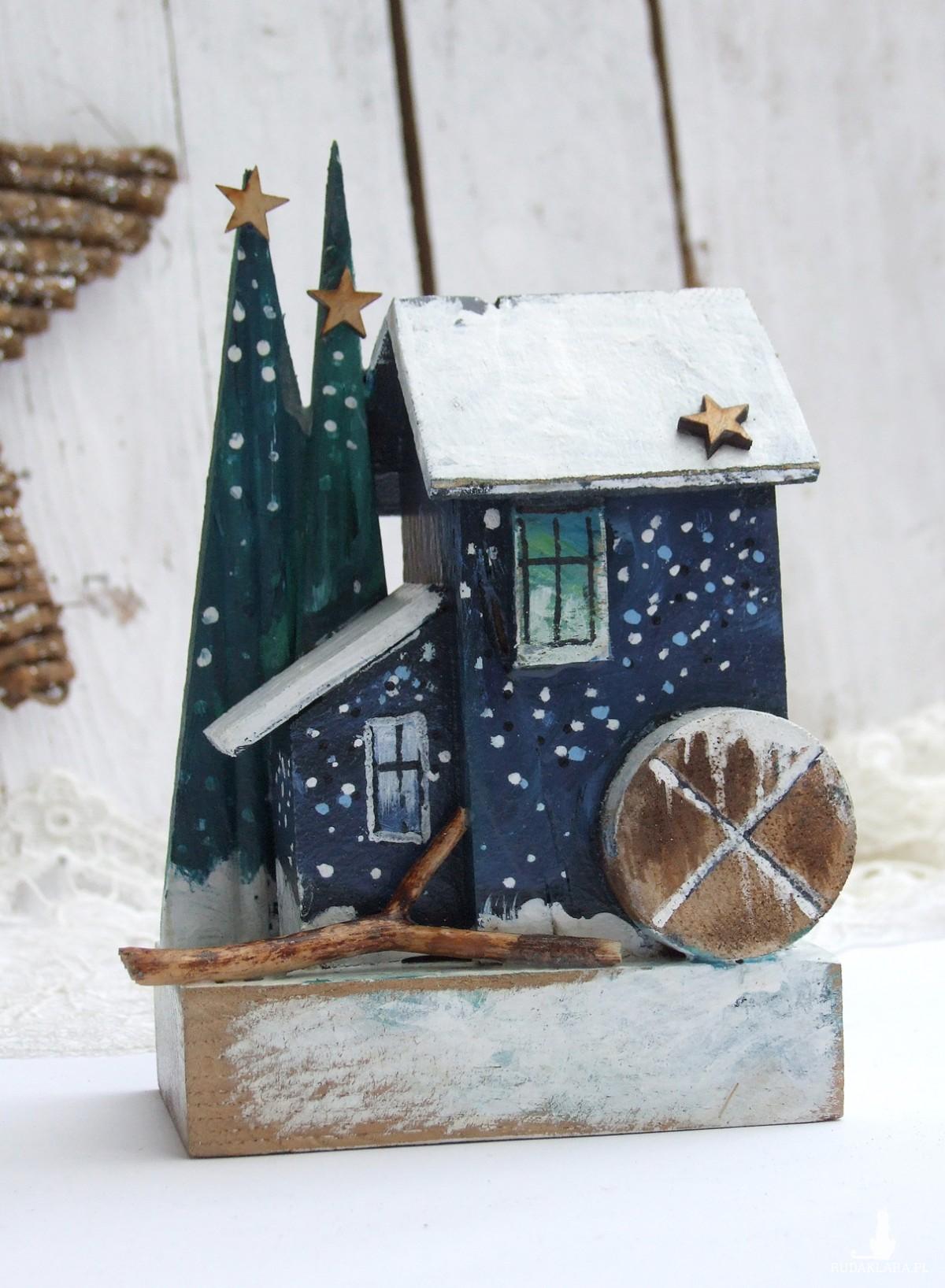 Drewniany domek dekoracyjny z choinkami