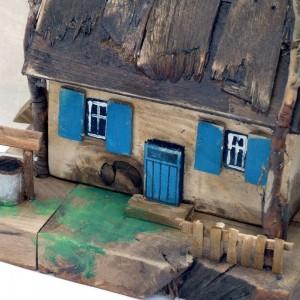 Chałupa z niebieskimi okiennicami i studnią